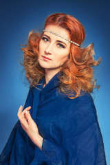 Art studio beauty portrait of young woman with red hair on blue background
