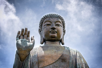 Portrait of a giant seated Buddha with a raised right hand..