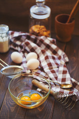 Baking cake ingredients - bowl, flour, eggs, egg whites foam on wooden background . Cooking course or kitchen mess poster concept