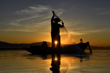 Silhouettes of the traditional stilt fishermen at sunset