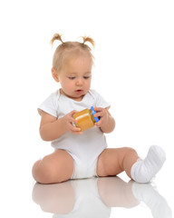 Infant Baby girl kid sitting and holdingin hands jar of child ma