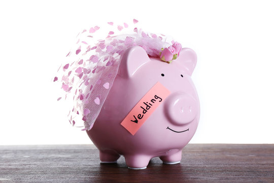 Piggy bank with wedding veil on wooden table, on white background