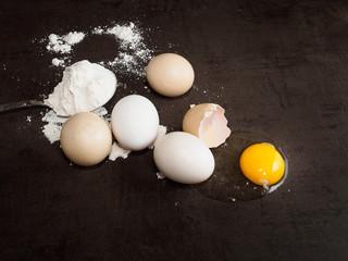 Broken egg and flour on dark background