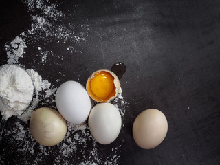 flour and eggs on dark vintage background
