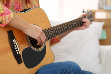 Female hands holding and playing western acoustic guitar closeup