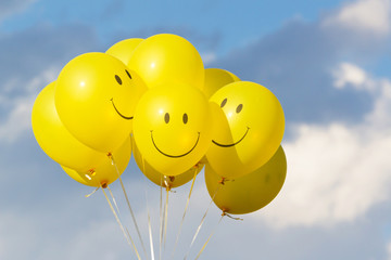 Yellow balloon smile  with  sky and clouds.