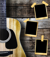 Guitar and old photo frame on wood background.