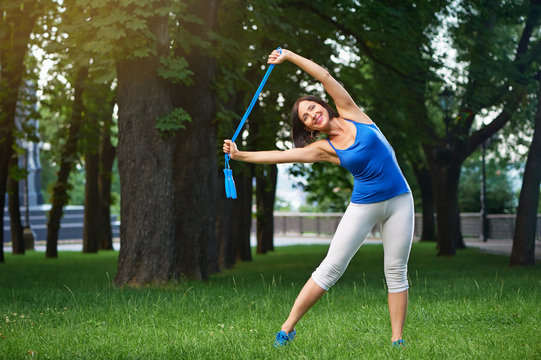 Happy middle aged woman working out with jumping rope