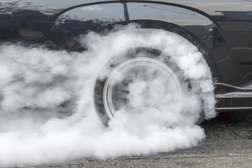 Drag racing car burns rubber off its tires