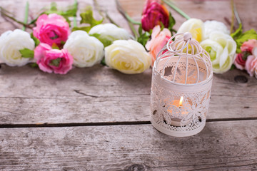 Candle in lantern  and flowers on vintage wooden background.