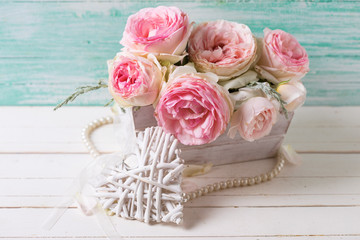 Pink roses flowers  in wooden box and  decorative heart  on whit