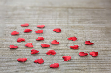 Heart shaped confetti on wooden background