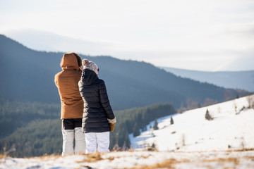 man and woman taking pictures in mountains
