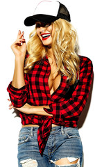 portrait of beautiful happy cute smiling blonde woman bad girl in casual red hipster winter checkered flannel shirt and blue jeans clothes with red lips and cap, big tits