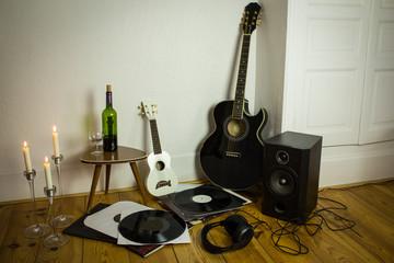 Rock'n'roll setup with ukulele, acoustic guitar, speaker, candle