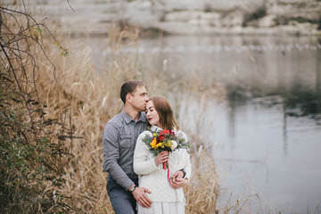 Winter wedding. Beautiful young couple posing near lake
