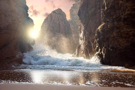Fantastic big rocks and ocean waves at sundown time. Dramatic