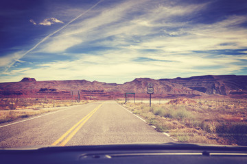 Vintage filtered road, photo taken from the front seat of a car, travel concept.