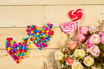Roses flowers  with heart shape candy on wooden background Paste