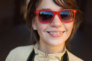 The girl in red sunglasses smiling
