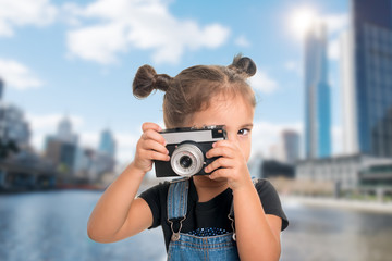 A liitle cute  girl taking picture  with vintage camera