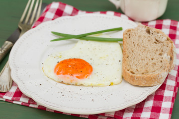 fried egg heart with green onion on white plate on green background