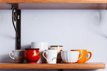 Many different cups are on the shelf.