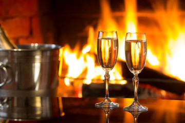 Two glasses of sparkling white wine and ice bucket  in front of warm fireplace. Romantic, cozy relaxed magical atmosphere near fire. Valentines day concept