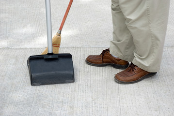 Person Sweeping with Broom and Dustpan