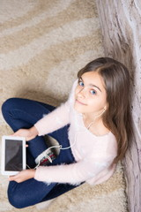 teen child playing on ipad sitting on a carpet at home