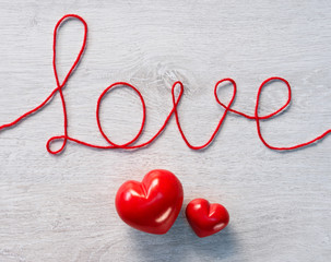 "Red hearts and word ""love"" on a white wooden background. Valentines Day background"