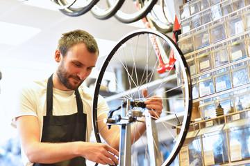 Laufradbau - Mechaniker zentriert Laufrad eines Fahrrades in der Werkstatt // Wheel building - mechanic centered wheel of a bicycle in the shop