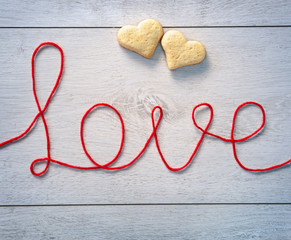 """Word """"love"""" and cookies on white wooden background. Valentines Day background. View from above."""