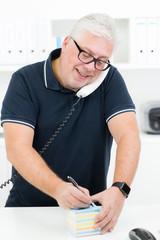 senior macht sich Notizen zum Telefongespräch