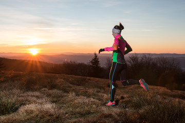 woman in colorful sportswear training for fitness in the sunset on the cold spring mountain trail