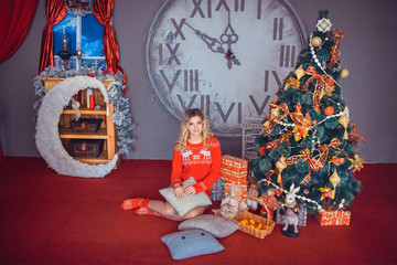 the girl sitting beside decorated Christmas tree