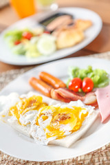 bread with scrambled eggs in white plate.