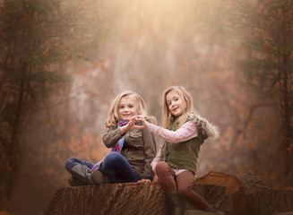 artistic outdoor portrait of two blond girls sitting on a log of tree in a woods