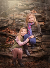 artistic outdoor portrait of two blond girls sitting on rocks