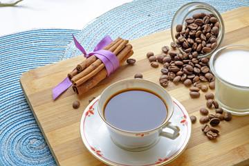 Coffee cup beans milk and cinnamon sticks landscape side crop