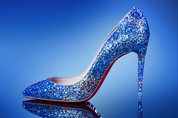 Woman shoe on high heel on the blue background.