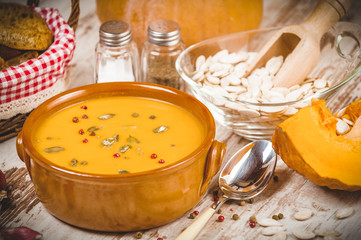 Homemade pumpkin soup in a clay bowl on rustic white table