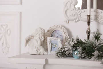white framework for photos and a figurine of an angel