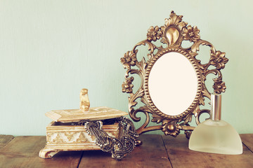 Antique blank victorian style frame, perfume bottle and neckless on wooden table. retro filtered image. template, ready to put photography