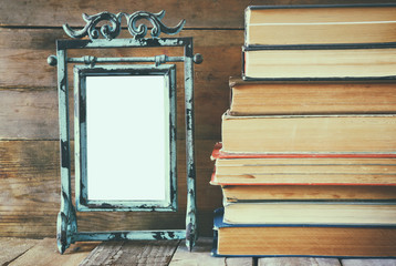 stack of old books next to vintage blank frame wooden table. vintage filtered image