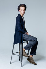 Young man posing with a trendy outfit wearing black hat and sitting on chair