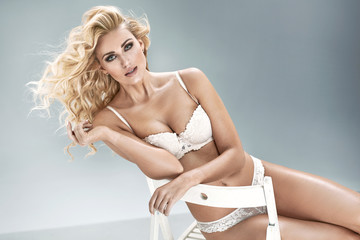 Portrait of beautiful blond young woman in white sexy lingerie