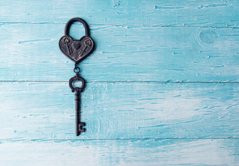 Heart and key on blu wooden background
