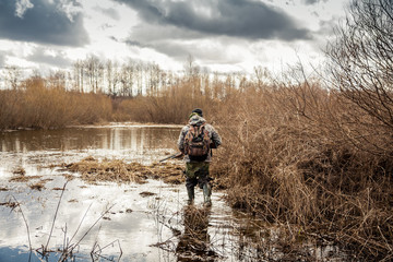 Foto auf Gartenposter Jagd hunter man creeping in swamp during hunting period