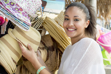 Mixed race woman shopping for hats at market stall